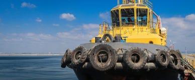 De sleepboot is bij de pijler in de zeehaven stock afbeeldingen