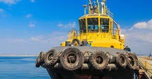 De sleepboot is bij de pijler in de zeehaven stock foto