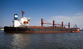 De sleepboot leidt het schip in haven. Stock Afbeeldingen
