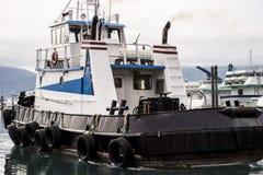 De sleepbootboten trekt zich van een dok in de visserijwateren terug van Alaska stock fotografie