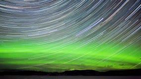 De slepen van de ster en Noordelijke lichten in nachthemel stock afbeelding