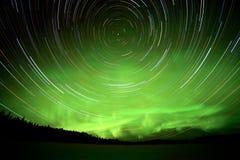 De slepen van de ster en Noordelijke lichten in nachthemel stock foto