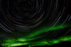 De slepen van de ster en Noordelijke lichten in nachthemel royalty-vrije stock foto