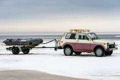 De de slepende aanhangwagen en boot van Lada Niva Stock Foto's