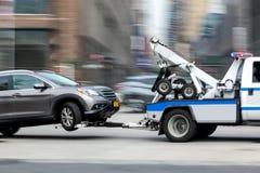 De slepenvrachtwagen levert het beschadigde voertuig stock fotografie