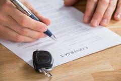 De Sleutel van BusinesspersonHolding Pen On Contract With Car op het Stock Fotografie