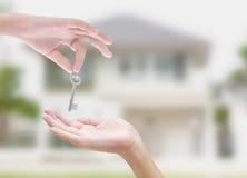 De sleutel van de handholding op huis en aardachtergrond Stock Foto's
