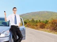De sleutel van de jonge mensenholding en het leunen op een auto Stock Afbeeldingen