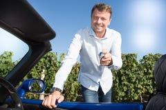 De sleutels die van de de holdingsauto van de mensenbestuurder zijn nieuwe auto drijven Stock Foto