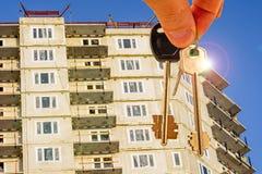 De sleutels tot de flat op de achtergrond van blauwe hemel en wolken Stock Foto