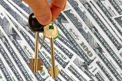 De sleutels tot de flat op de achtergrond van geld Stock Foto's