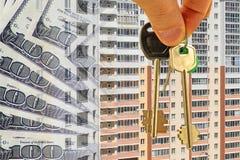 De sleutels tot de flat op een achtergrond van geld en huizen Stock Foto's