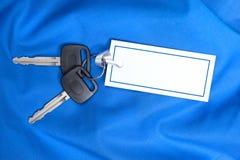 De Sleutels van de auto en giftkaart op blauw Stock Foto's