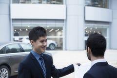 De sleutels van de de holdingsauto van de autoverkoper en administratie en het verkopen van een auto aan een jonge zakenman Royalty-vrije Stock Foto's