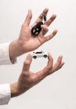 De sleutels van de mensenholding en kleine auto Royalty-vrije Stock Foto's