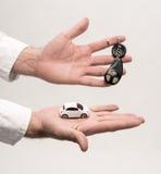 De sleutels van de mensenholding en kleine auto Stock Fotografie