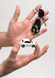 De sleutels van de mensenholding en kleine auto Stock Foto