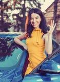 De sleutels van de vrouwenholding tot nieuwe auto en het glimlachen bij camera op een achtergrond van een huis stock afbeelding
