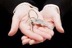 De sleutels van een makelaar in onroerend goedholding tot een nieuw huis in haar handen. Stock Foto