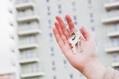 De sleutels van een makelaar in onroerend goedholding tot een nieuwe flat in haar handen. stock afbeelding