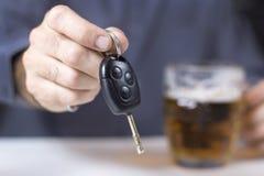 In de sleutels van de voorgrondauto in een mannelijke hand worden gehouden die Een biermok op de achtergrond royalty-vrije stock foto