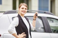 De sleutels van de vrouwenholding tot nieuwe autoauto en het glimlachen bij camera stock foto's