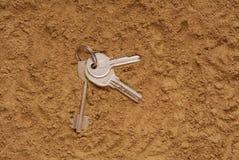 De sleutels zijn op het zand stock afbeeldingen