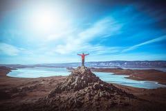De slijtage rode kleren van de reizigersmens en het opheffen van wapen die zich op de piek van berg dichtbij Meer Baikal, Siberië stock afbeelding
