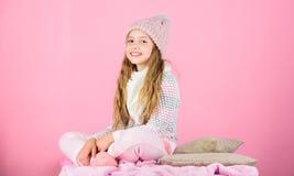 De slijtage van het jong geitjemeisje breide zachte hoeden roze achtergrond Houd breigoed na was zacht Zachte gebreide toebehoren stock foto's