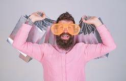 De slijtagezonnebril van mensen gebaarde hipster terwijl partij het winkelen zakken draag Het winkelen op Zwarte Vrijdag Het gelu stock foto