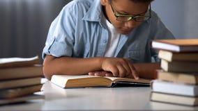 De slimme Afro-Amerikaanse boeken van de jongenslezing, boekenwurmjong geitje, weinig nerd, onderwijs royalty-vrije stock afbeeldingen