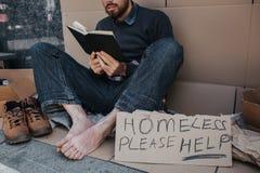 De slimme dakloze mens zit op karton en leest een boek Hij is zeer geconcentreerd op dat Er zijn sigh die stock foto's