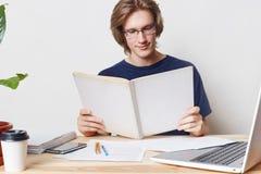 De slimme harde werkende modieuze mannelijke student draagt bril, heeft aandachtige starende blik in boek, leest wetenschappelijk Stock Foto's