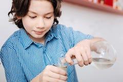 De slimme jonge flessen van de jongensholding met chemische vloeistoffen Stock Foto's