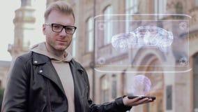 De slimme jonge mens met glazen toont een conceptueel hologram moderne Suv stock video