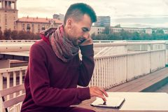 De slimme jonge mens werkt in openlucht aan tabletcomputer in koffie in stedelijke openbare ruimte stock foto's