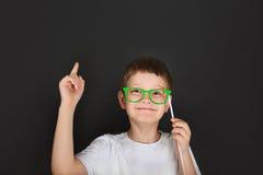 De slimme jongen met groene glazen is nadenkend dichtbij bord Stock Foto's