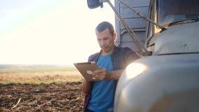 De slimme landbouw de bestuurderstribunes van de mensenlandbouwer met een levensstijl digitale tablet dichtbij de vrachtwagen lan stock video