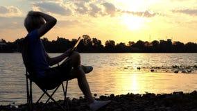 De slimme Mens zit op een Vouwende Stoel en bekijkt Zijn Tabletpc Zonsondergang stock videobeelden