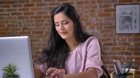 De slimme mooie cauasndame typt op haar geconcentreerd laptop terwijl het zitten in baksteenbureau bij haar Desktop, die zijn stock video