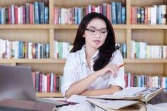 De slimme student leert met boeken in bibliotheek Stock Afbeelding