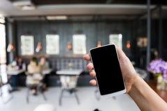 De slimme telefoon van de handgreep, mobiel over vaag beeld van koffiewinkel stock foto