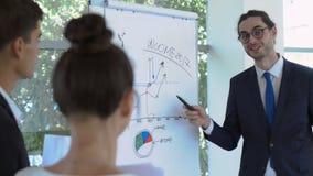 De slimme zakenman vertelt over de inkomens van bedrijf aan de collega's stock footage
