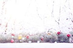De slinger van de Kerstmisspar op houten raad op venstervensterbank over het parkachtergrond van de aard sneeuwende boom met exem Stock Foto