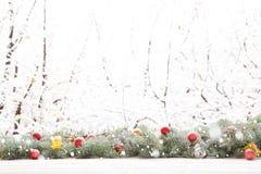 De slinger van de Kerstmisspar op houten raad op venstervensterbank over het parkachtergrond van de aard sneeuwende boom met exem Royalty-vrije Stock Foto's