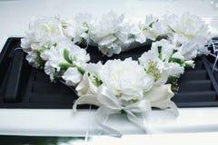De slinger van witte bloemen ligt op de auto Stock Afbeeldingen