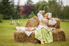 De slokjes van de boervrouw op het hooi royalty-vrije stock afbeeldingen