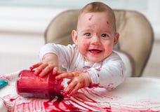 De slordige en vuile baby eet snack met handen stock fotografie