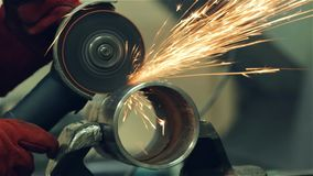 De slotenmaker maakt een gelaste naad op een sectie van een staalpijp schoon stock footage
