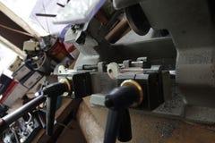 De slotenmaker in workshop maakt nieuwe sleutel Beroeps die sleutel in slotenmaker maken Persoon die maakt en sleutels en sloten  Stock Afbeelding